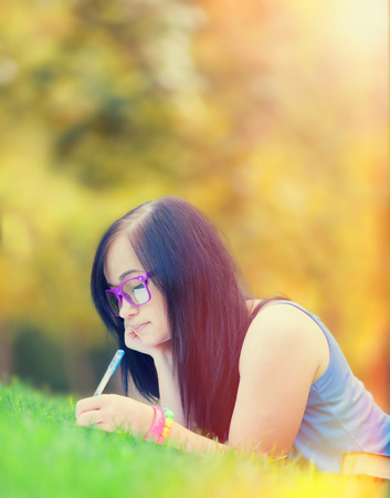 Teen girl with notebook in the park. photo