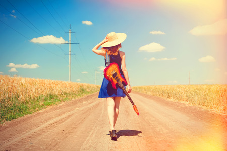 the enchantress: Rock girl with guitar at countryside.