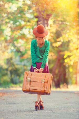 Beautiful redhead girl with suitcase in the park. Zdjęcie Seryjne