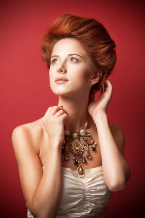 historical clothing: Portrait of redhead edvardian women with necklace on red .