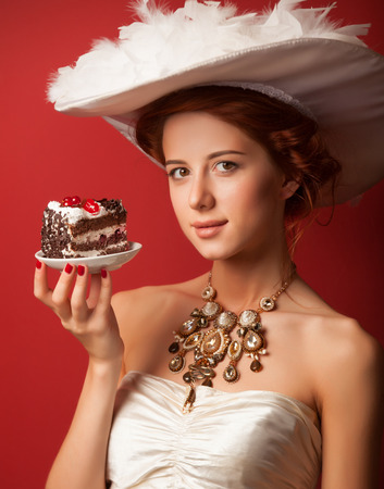 sweettooth: Portrait of redhead edvardian women with cake on red background.