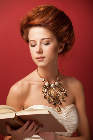 Portrait of redhead edvardian women with book on red background. photo