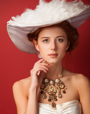 Portrait of redhead edvardian women on red background. photo
