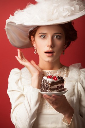 sweettooth: Portrait of redhead edvardian women with cake on red .