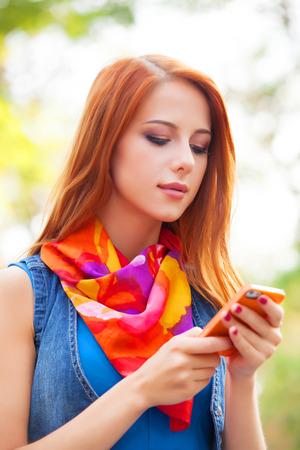 beautifu: Beautifu girl with mobile phone in the park. Stock Photo
