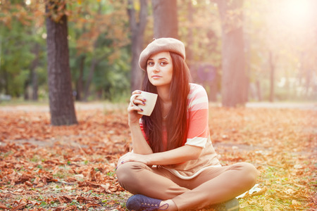 Beautiful brunette girl with cup in the park. Stock Photo