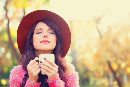 Brunette girl wtih cup of coffee in the autumn park. photo