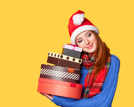 Redhead girl with gifts on yellow background photo