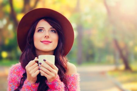 秋の公園でコーヒーのカップとブルネットの少女。 写真素材