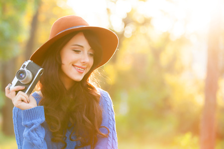 Brunette girl with camera in the park in sunset time photo