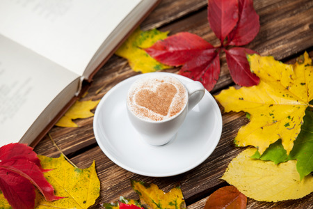Autumn leafs, book and coffee cup on wooden table. photo