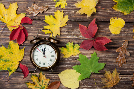 Autumn leafs and alarm clock on wooden table. photo