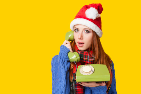 Beautiful redhead girl in christmas hat with telephone on yellow background.