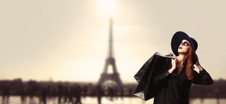 poses de modelos: Mujer pelirroja con bolsas de compras en el fondo parisino.