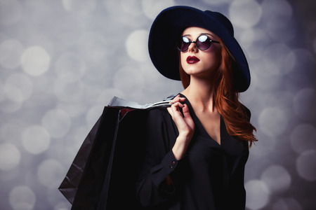 Style redhead girl with sunglasses and shopping bags.