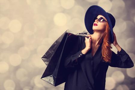 スタイルの買い物袋で赤毛の女の子.