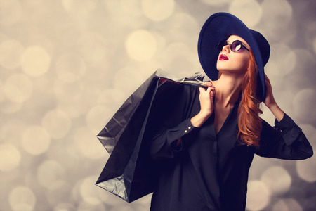 Style redhead girl with shopping bags. photo