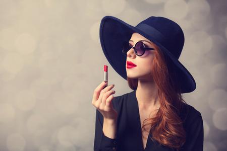 赤毛サングラス、口紅と女性をスタイルします。 写真素材