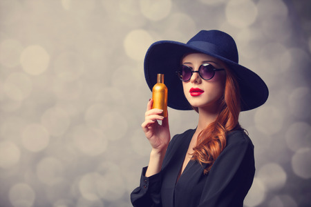 Style redhead girl in a hat holding perfume photo