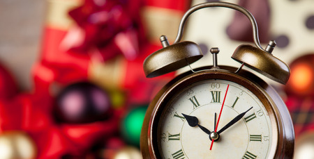 Alarm clock and christmas gifts on background. photo