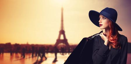 luxury goods: Mujer pelirroja con bolsas de compras en el fondo parisino.