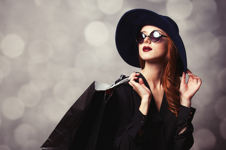 hang body: Style redhead girl with sunglasses and shopping bags.