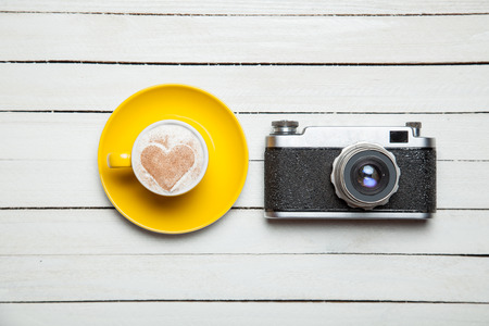 retro camera: Retro camera and cup of coffee on wooden table. Stock Photo
