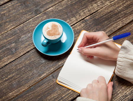 persona escribiendo: Mano femenina escribiendo algo en el cuaderno cerca de la taza de caf�.