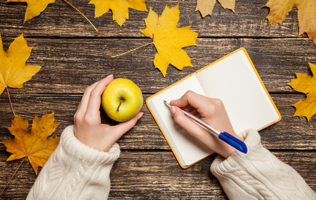 Female hand writing something in to notebook and holding apple photo