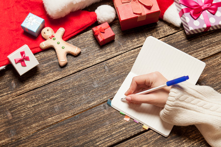 Female writing wish list in to notebook near christmas gifts photo