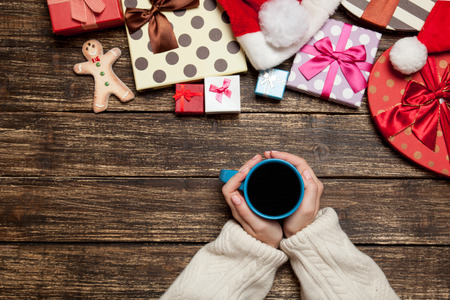 women holding cup: Female holding cup of coffee on wooden table near christmas gifts