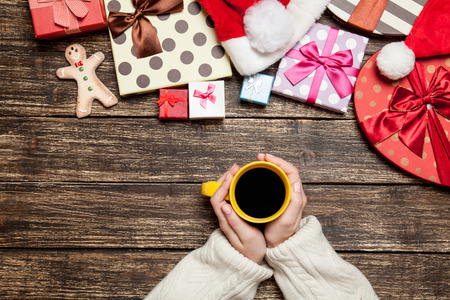 Female holding cup of coffee on wooden table near christmas gifts photo