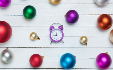 Alarm clock and christmas balls on white table. photo