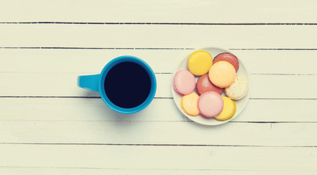 Cup of coffee and macaron on wooden table. photo