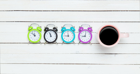 Four alarm clocks and cup of coffee photo