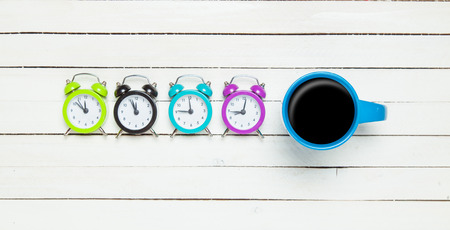 cup four: Four alarm clocks and cup of coffee
