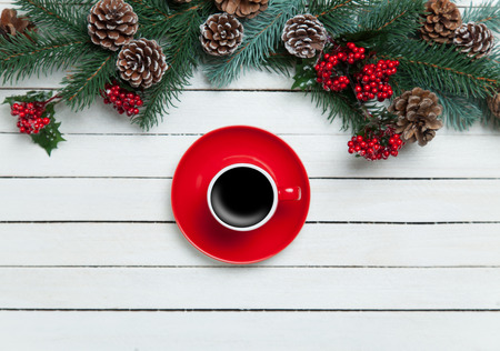 Hot coffee on wooden table near pine branches photo