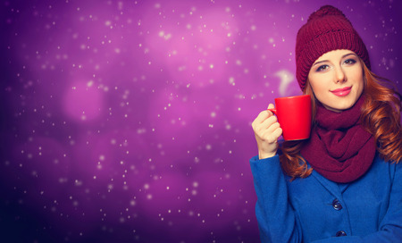 Smiling redhead girl with cup on violet background. photo