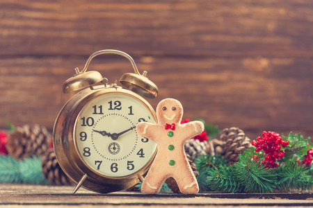 time table: Alarm clock near Pine branches and gingerbread on wooden table. Stock Photo