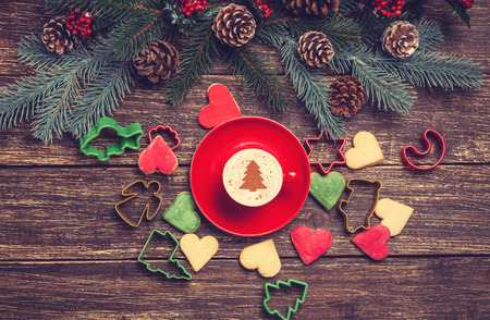 Hot cappuccino with christmas tree shape and cookie on a wooden table near pine branches photo