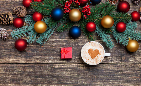 Hot cappuccino with heart shape and gift on a wooden table near pine branches photo