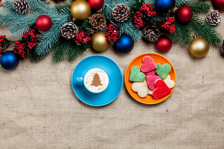 Hot cappuccino with christmas tree shape and cookie on a table near pine branches photo
