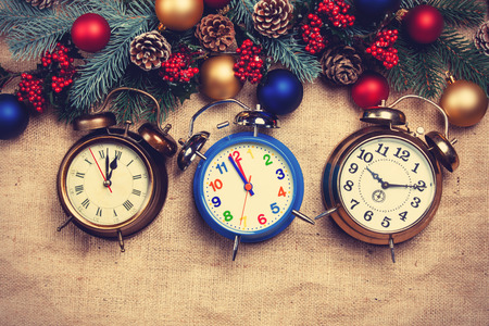 pine three: Three Alarm clocks near Pine branches on a table. Stock Photo