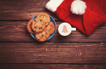 Cookie and cup of coffee with santas hat on wooden table. Photo in retro color image style.