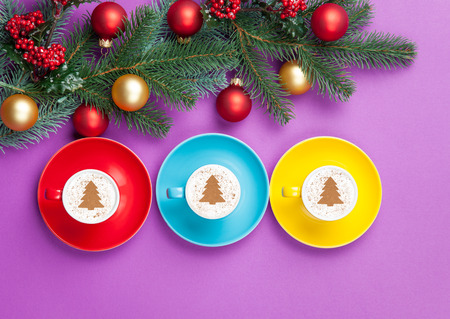 pine three: three cappuccinos with christmas tree shape and pine branch on violet background.