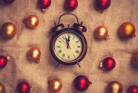 reloj antiguo: Reloj de alarma retro de oro y bolas rojas en fondo del yute.