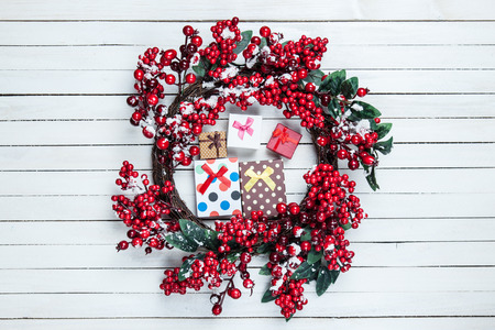 Holly christmas wreath with gift boxes on wooden table. photo