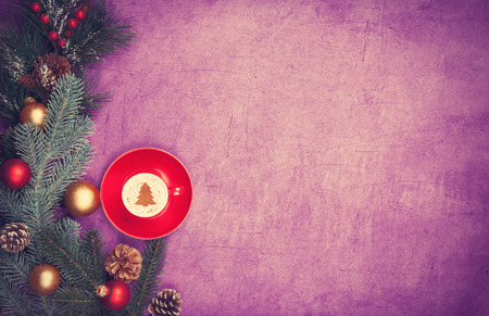 Cappuccino with christmas tree shape and pine branch on violet background. photo