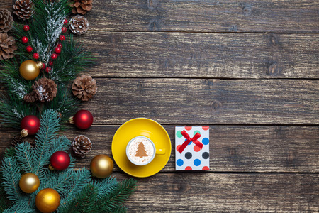 Cappuccino with christmas tree shape and gift on wooden table. photo