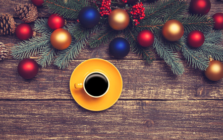 Hot coffee on a table near pine branches with chritmas balls on wooden table. photo